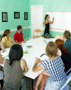 a teacher writing on a whiteboard with students around a table in the classroom