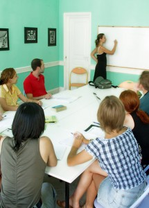 a teacher writing on a whiteboard with students watching her