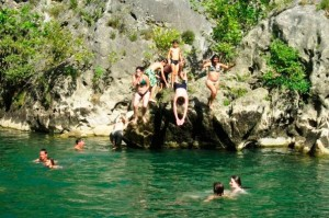 young people swimming and diving off rocks into a lake